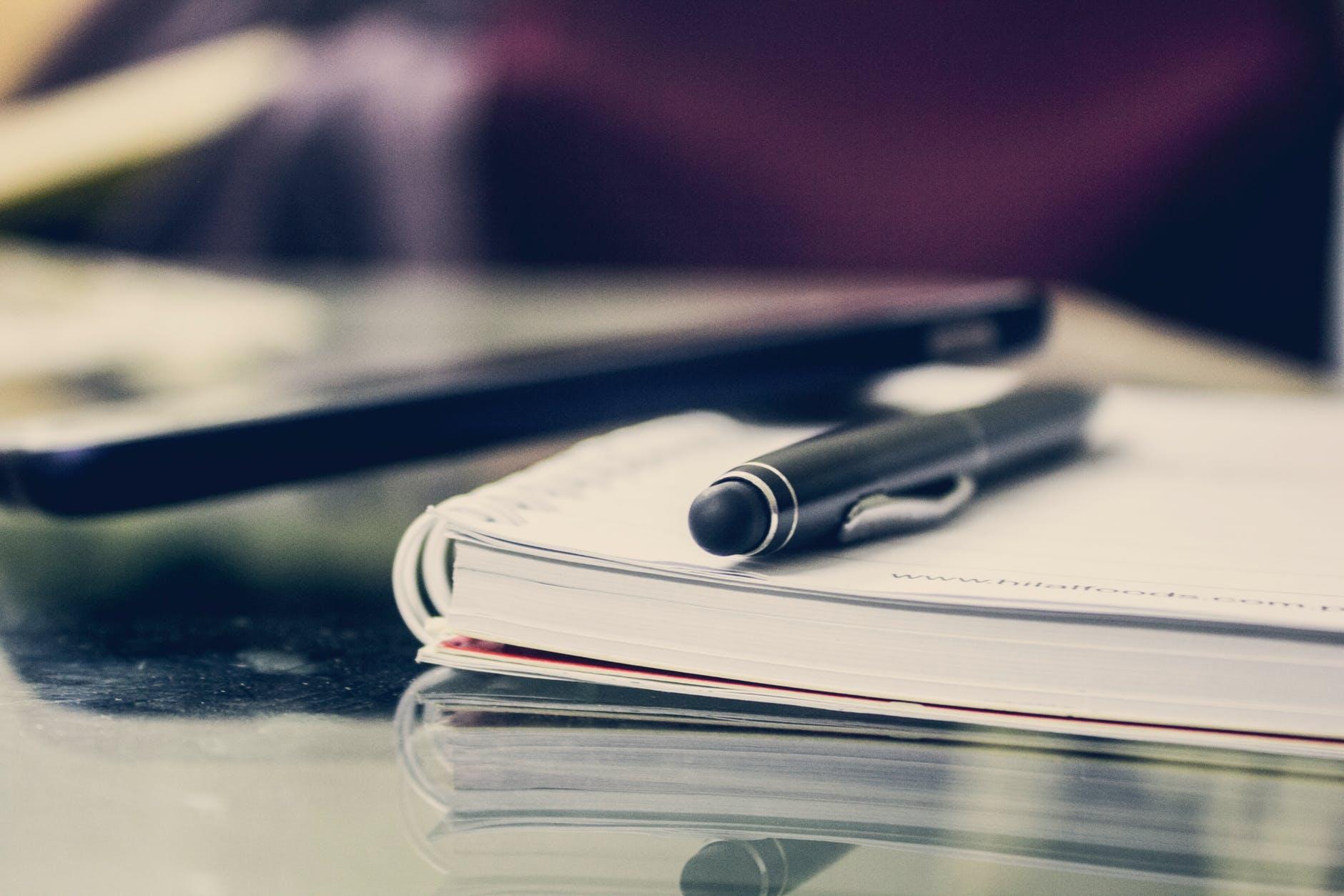 black twist pen on notebook